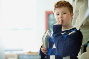 Elementary student making be quiet gesture.